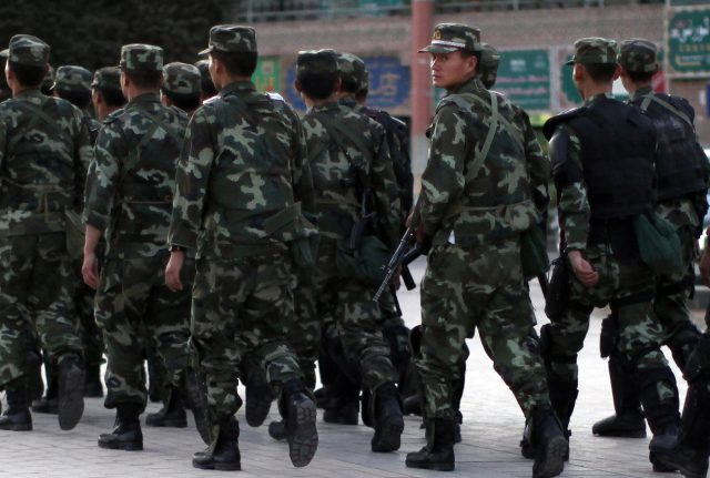 Armed police officers patrol an ethnice Uighur area in Kashgar, in Xinjiang province