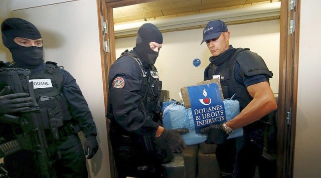 French armed customs officers stand guard in front of a storage room with seized cannabis in Paris, France October 18, 2015. REUTERS/Jacky Naegelen